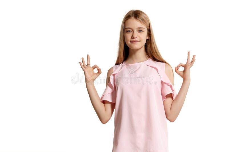 Retrato del estudio de un adolescente rubio de la muchacha hermosa en una presentación rosada de la camiseta aislado en el fondo  imagenes de archivo