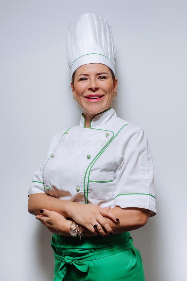 Retrato del estudio de un cocinero hermoso de la mujer en uniforme Un cocinero sonriente de la mujer en un casquillo y un uniform fotos de archivo libres de regalías