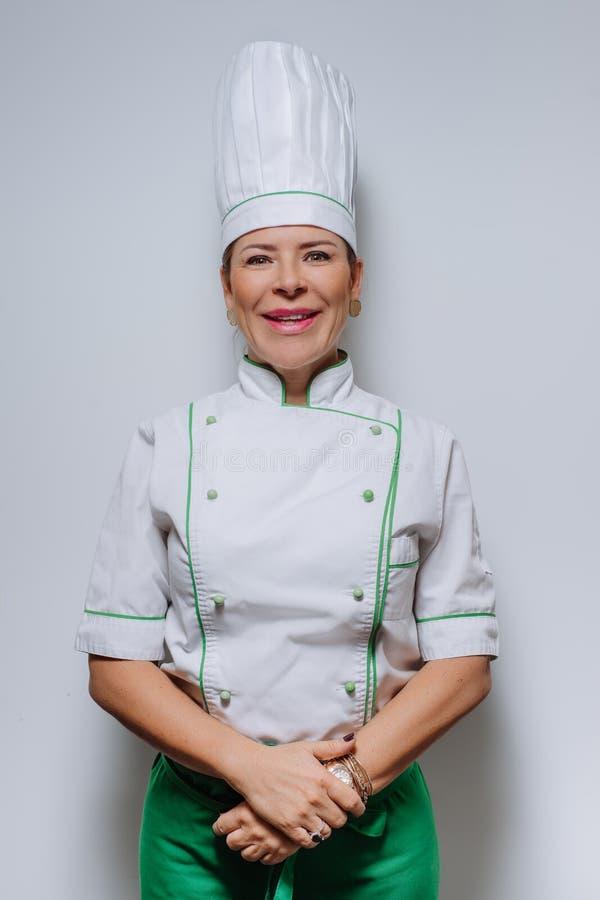 Retrato del estudio de un cocinero hermoso de la mujer en uniforme Un cocinero sonriente de la mujer en un casquillo y un uniform imágenes de archivo libres de regalías