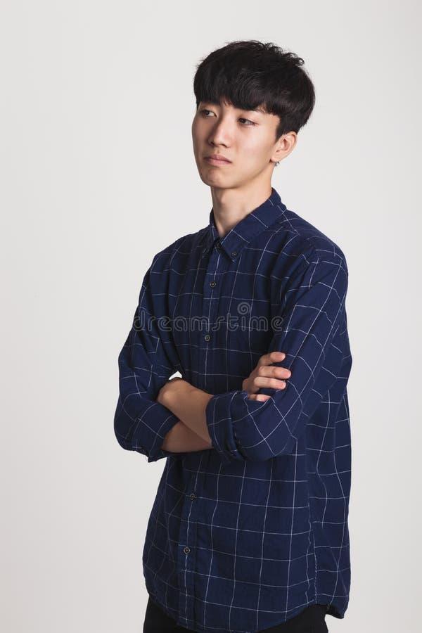 Retrato del estudio de un hombre joven asiático con la decepción en algo imagen de archivo