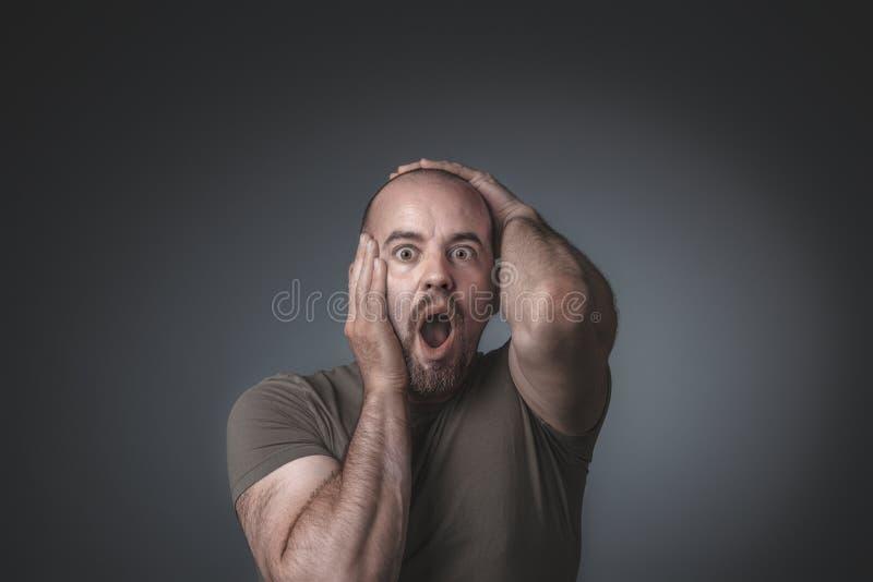 Retrato del estudio de un hombre que lleva a cabo su cabeza, la expresión de la sorpresa y el miedo fotos de archivo