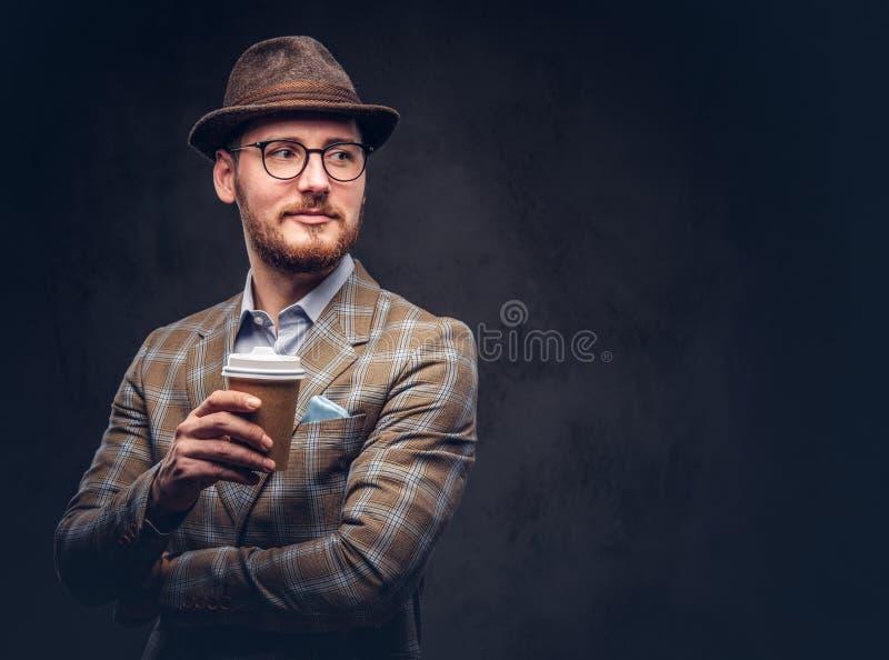 Retrato del estudio de un inconformista barbudo en llevar del sombrero y de los vidrios fotos de archivo