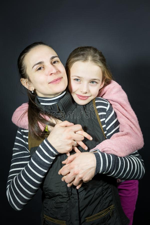 Retrato del estudio de una madre y de una hija cariñosas, blando y fuertemente abrazando y llevando a cabo las manos imágenes de archivo libres de regalías