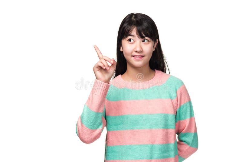 Retrato del estudio de una mujer asiática del este adolescente que señala con el finger en alguna parte imagen de archivo