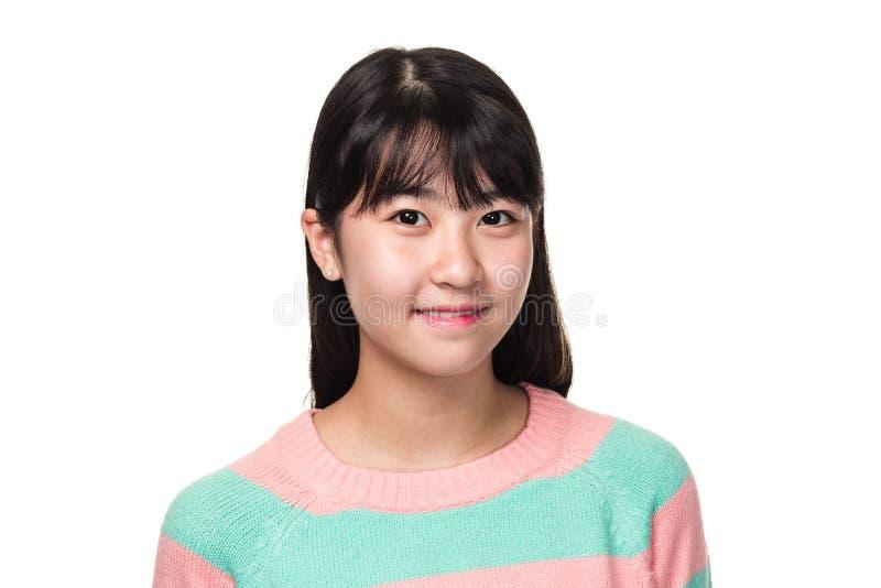 Retrato del estudio de una mujer asiática del este adolescente que sonríe y que mira en alguna parte fotos de archivo libres de regalías