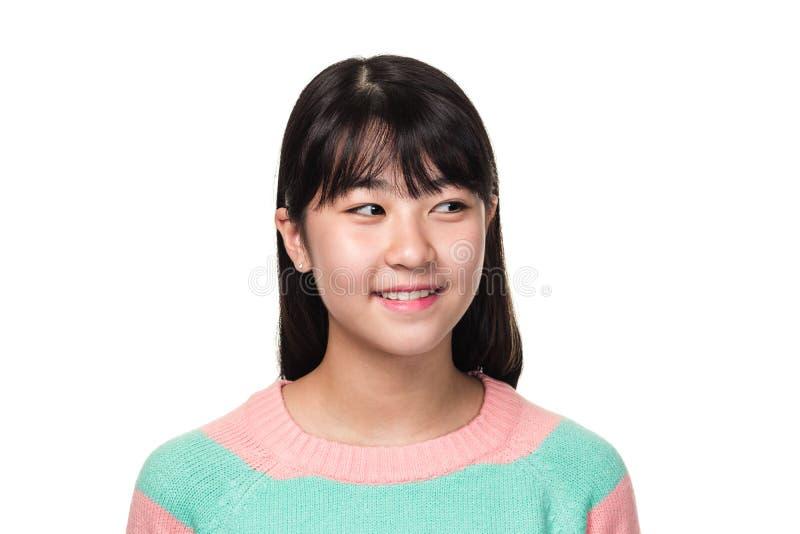 Retrato del estudio de una mujer asiática del este adolescente que sonríe y que mira en alguna parte imágenes de archivo libres de regalías
