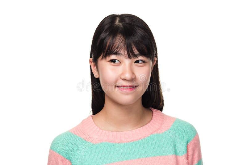 Retrato del estudio de una mujer asiática del este adolescente que sonríe y que mira en alguna parte fotos de archivo