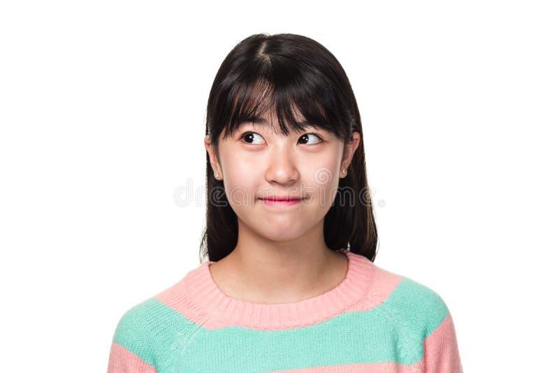 Retrato del estudio de una mujer asiática del este adolescente que sonríe y que mira en alguna parte fotografía de archivo