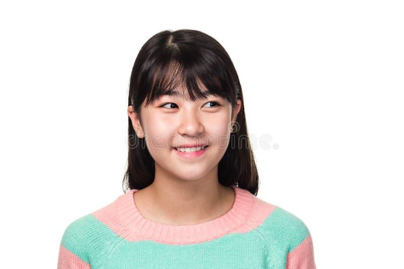 Retrato del estudio de una mujer asiática del este adolescente que sonríe y que mira en alguna parte foto de archivo