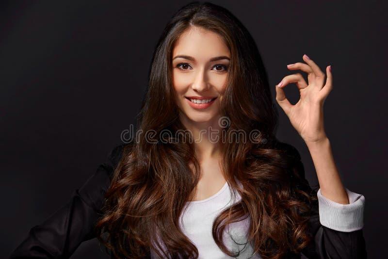 Retrato del estudio de una mujer atractiva que da la muestra ACEPTABLE a la cámara fotografía de archivo