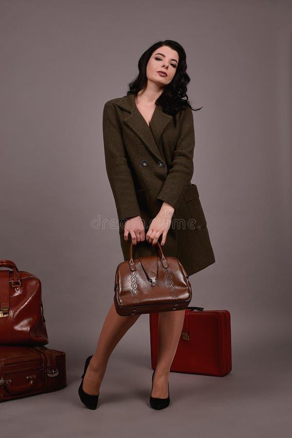 Retrato del estudio de una mujer en la capa clásica que presenta con el sistema de maletas y del bolso retros en un fondo gris imagen de archivo libre de regalías