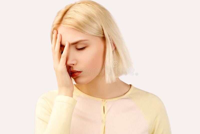 Retrato del estudio de una mujer joven Ella pone su mano a su cara en verg?enza y la frustraci?n El concepto de fracaso y de face imágenes de archivo libres de regalías