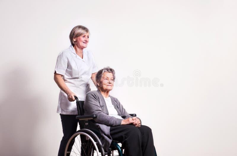 Retrato del estudio de una mujer mayor en silla de ruedas y una enfermera foto de archivo