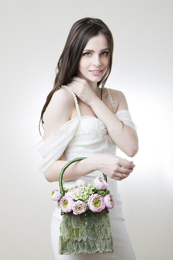 Retrato del estudio de una novia hermosa joven con su bolso en su mano foto de archivo libre de regalías