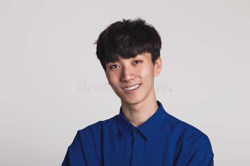 Retrato del estudio de una sonrisa asiática del hombre confiada y feliz foto de archivo