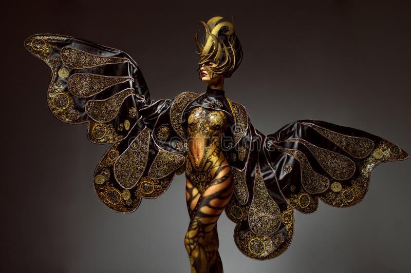 Retrato del estudio del modelo hermoso con arte de cuerpo de oro de la mariposa de la fantasía foto de archivo libre de regalías