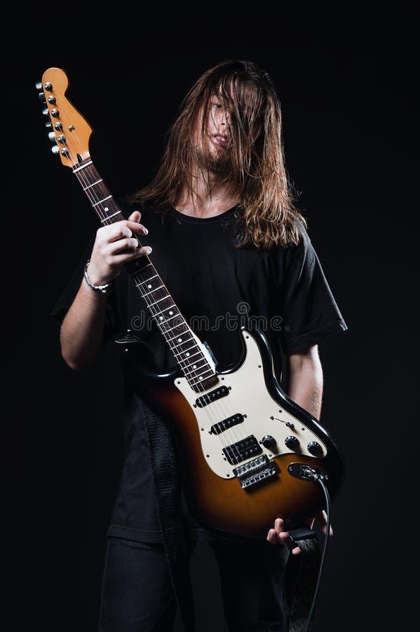 Retrato del estudio: el hombre joven hermoso con el músico largo de la roca del pelo sostiene la guitarra eléctrica en manos imágenes de archivo libres de regalías