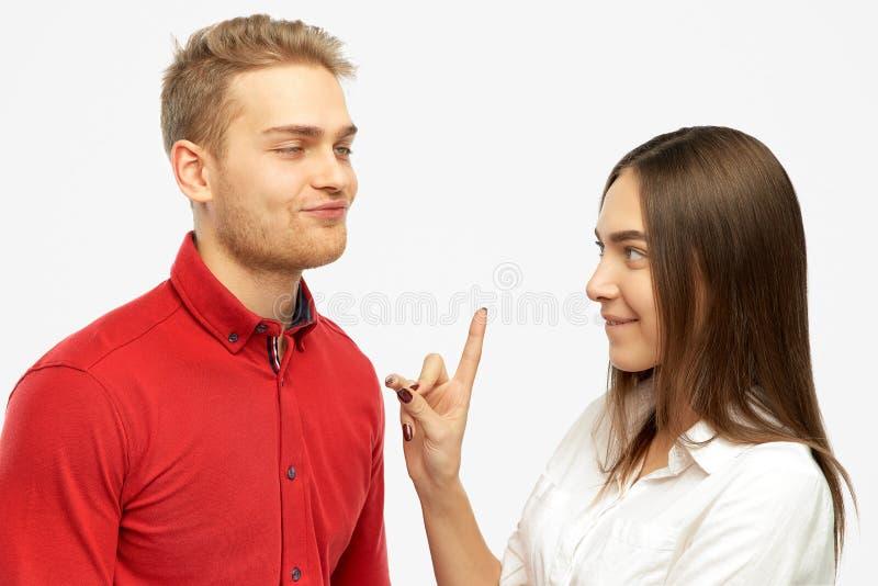 Retrato del estudio en un fondo aislado del beso de ofrecimiento del hombre rubio divertido joven a su novia fotos de archivo