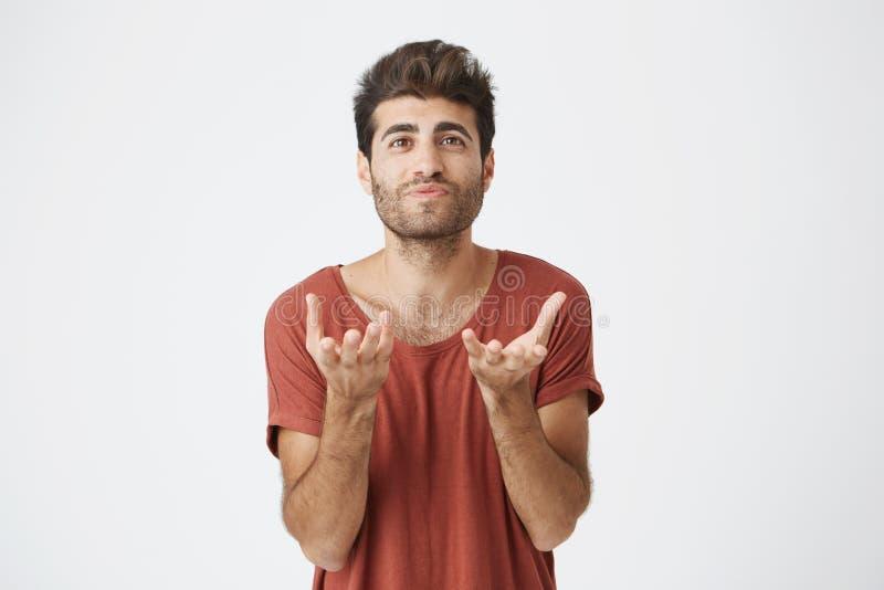 Retrato del estudio del estudiante barbudo atractivo en la camiseta roja que estira sus manos a la cámara Hombre emocional con fotos de archivo