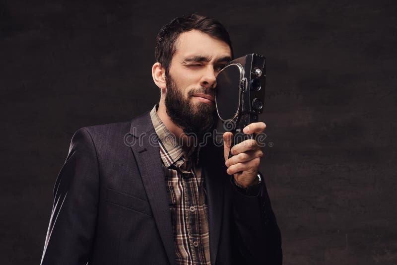 Retrato del estudio del hombre barbudo que lleva un traje clásico que sostiene una cámara retra, haciendo una foto fotos de archivo