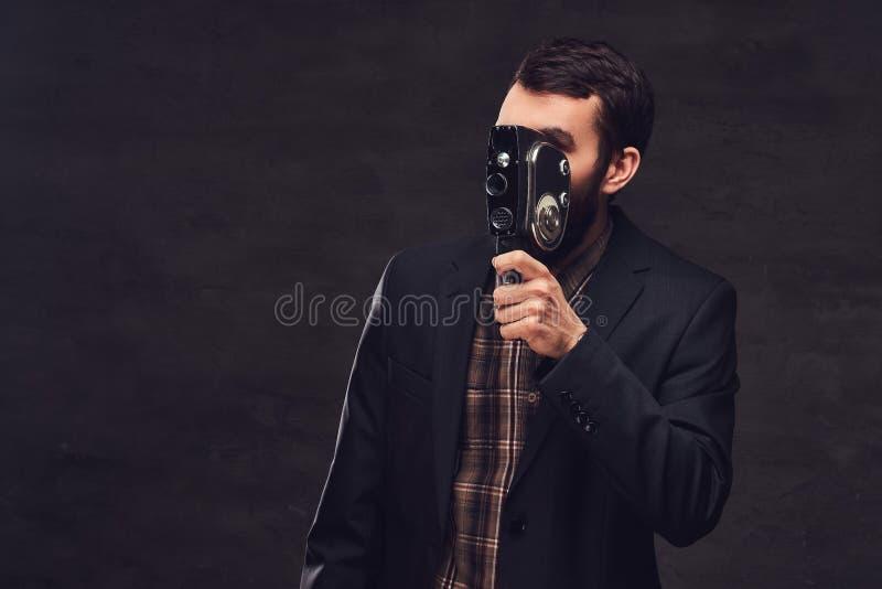 Retrato del estudio del hombre barbudo que lleva un traje clásico que sostiene una cámara retra, haciendo una foto imagen de archivo libre de regalías