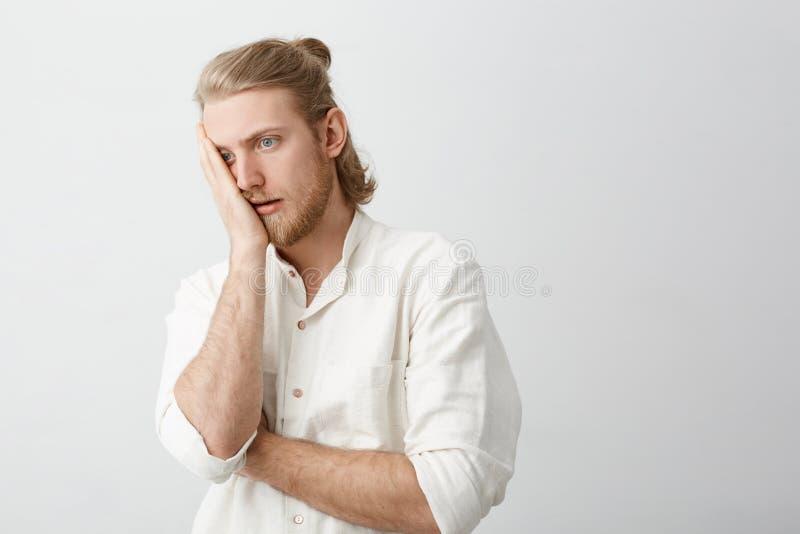 Retrato del estudio del hombre barbudo rubio hermoso que hace la palma de la cara con la expresión enfadada o cansada, oponiéndos fotografía de archivo libre de regalías