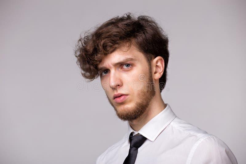 Retrato del estudio del hombre joven incr?dulo que es ofendido y trastornado, coloc?ndose sobre fondo gris, expresando tristeza y foto de archivo