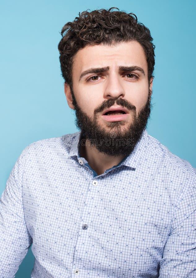 Retrato del estudio del hombre joven sorprendido con su boca abierta Barba negra fotos de archivo
