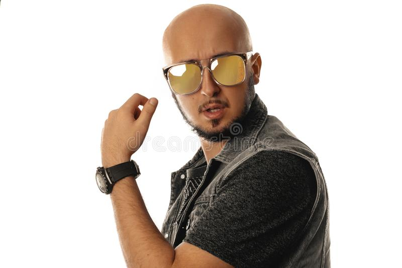 Retrato del estudio del machista joven magnífico en la presentación de las gafas de sol fotos de archivo libres de regalías
