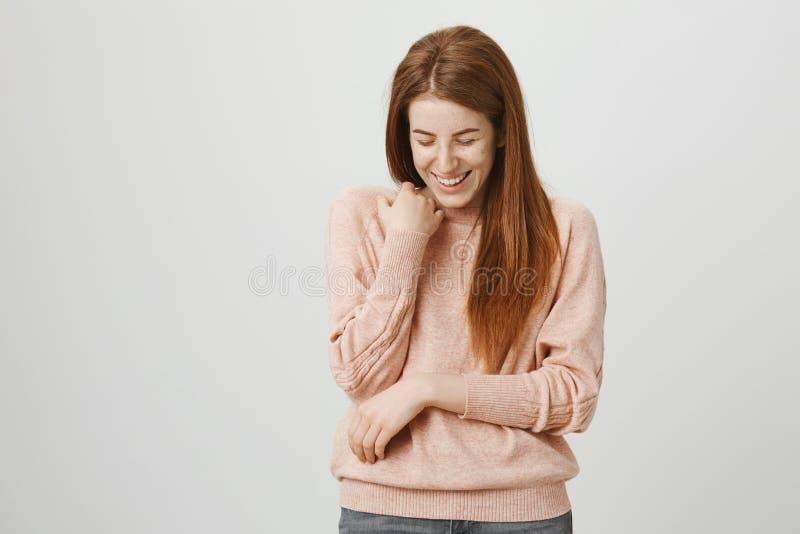 Retrato del estudio del modelo femenino del pelirrojo adulto feliz que ríe hacia fuera ruidosamente y que se coloca en actitud tí foto de archivo
