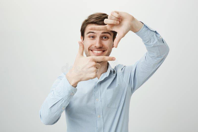 Retrato del estudio del productor joven hermoso en el finger de la camisa sport que enmarca y que sonríe alegre en la cámara, bus fotografía de archivo libre de regalías