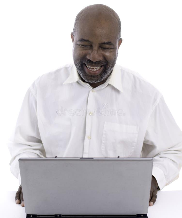 Retrato del experto afroamericano alegre del software que ríe mientras que sienta el frente de un ordenador portátil fotos de archivo