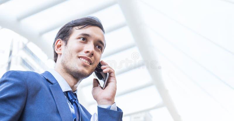 Retrato del exterior derecho del hombre de negocios asiático feliz usando el teléfono móvil fotografía de archivo