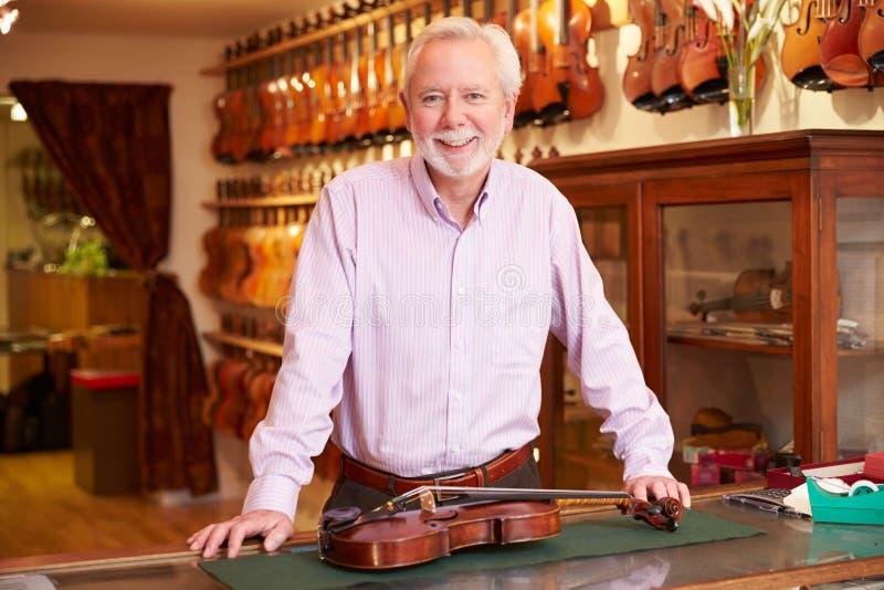 Retrato del fabricante del violín en tienda imagen de archivo