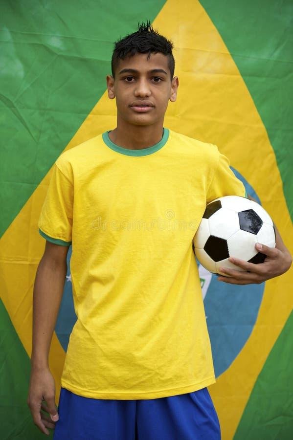 Retrato del fanático del fútbol brasileño joven patriótico orgulloso que presenta con la bandera imagen de archivo