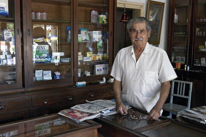 Retrato del farmacéutico mayor en su farmacia imagen de archivo