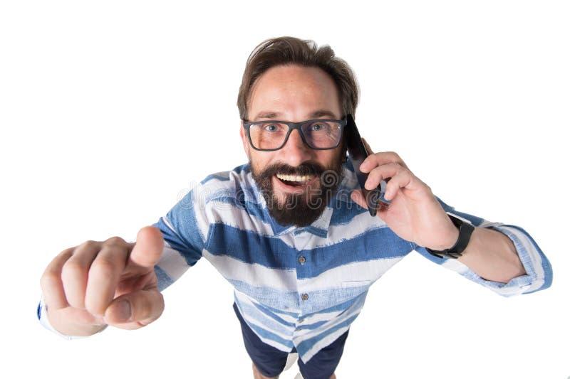 Retrato del fisheye del primer del hombre barbudo fresco que sonríe con el teléfono móvil y el finger del indicador en el fondo b imagenes de archivo