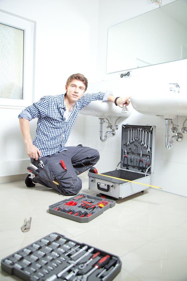 Retrato del fontanero de sexo masculino que fija un fregadero en cuarto de baño imagenes de archivo