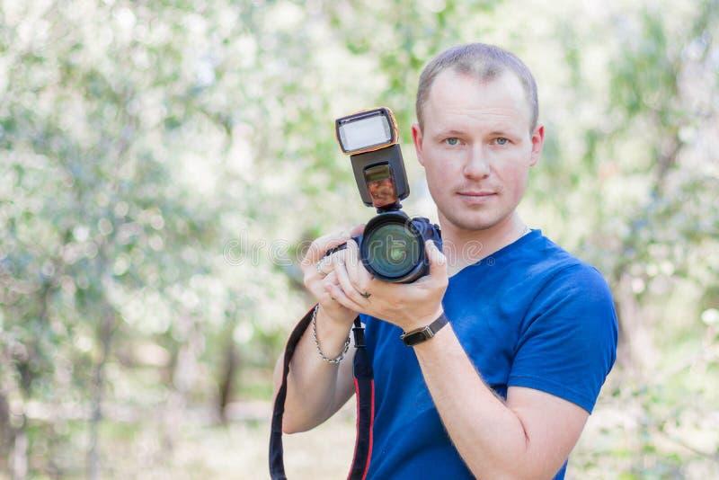 Retrato del fotógrafo de sexo masculino con una cámara en manos, camiseta azul que lleva de DSLR al aire libre el día de verano R fotografía de archivo