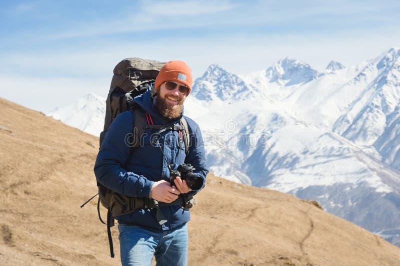 Retrato del fot?grafo de sexo masculino barbudo sonriente en gafas de sol contra la perspectiva de las monta?as coronadas de niev imagen de archivo