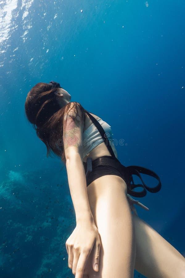 Retrato del freediver de la mujer joven bajo el agua fotos de archivo