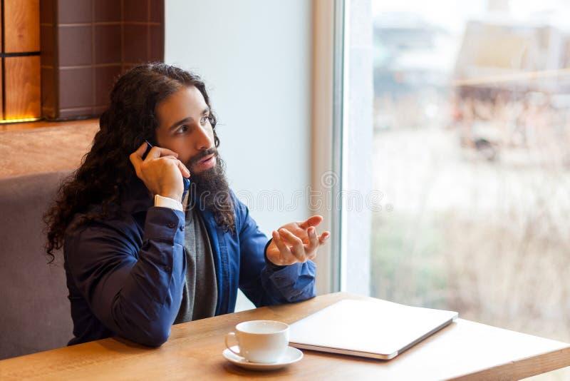 Retrato del freelancer adulto joven del hombre de la inteligencia hermosa seria en el estilo sport que se sienta en café con el o imagen de archivo