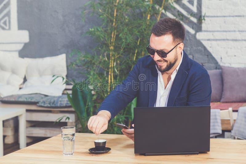 Retrato del freelancer alegre en el escritorio en cafetería foto de archivo
