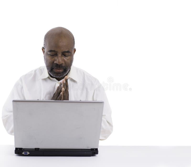 Retrato del frente que se sienta del experto afroamericano thoughful y pensativo del software de un ordenador portátil Comtemplac fotos de archivo
