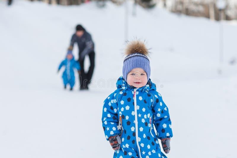 Retrato del gemelo lindo del muchacho en parque del invierno en fondo de su padre y hermano foto de archivo libre de regalías