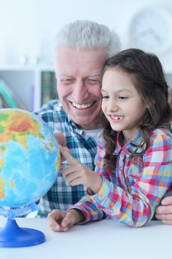 Retrato del globo de exploración del mundo del abuelo y de la nieta foto de archivo libre de regalías