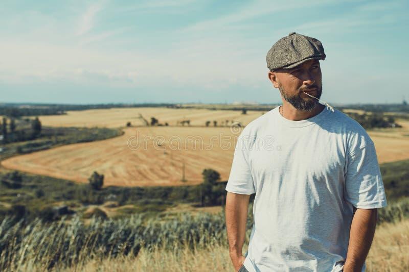 Retrato del granjero de sexo masculino confuso que mira en la c?mara y que rasgu?a su cabeza Ciérrese para arriba de la situación foto de archivo libre de regalías