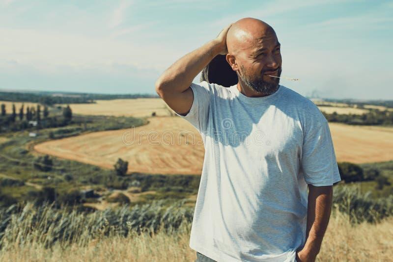 Retrato del granjero de sexo masculino confuso que mira en la c?mara y que rasgu?a su cabeza Ciérrese para arriba de la situación imagen de archivo