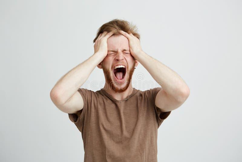 Retrato del griterío de grito del hombre enojado emocional del trastorno llevando a cabo el fondo blanco excesivo principal imágenes de archivo libres de regalías