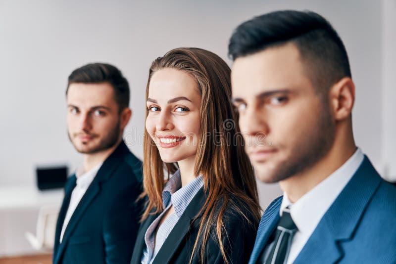 Retrato del grupo de hombres de negocios jovenes en fila en oficina foto de archivo